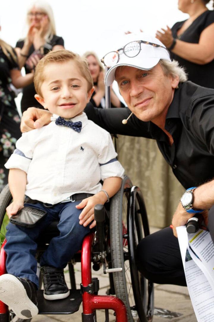 Garçon en fauteuil roulant posant avec un homme