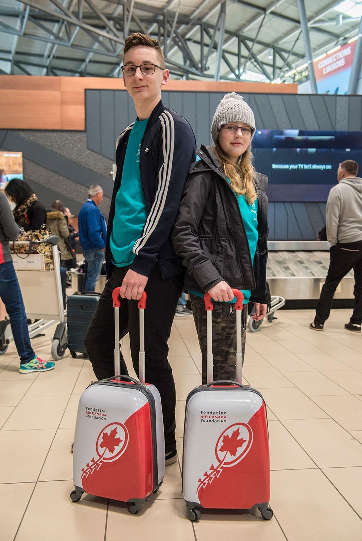 Deux adolescents à l'aéroport avec des valises d'Air Canada