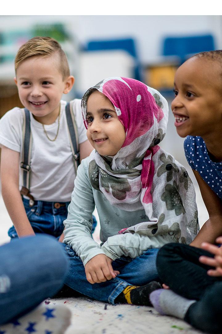 Trois enfants souriants assis en cercle