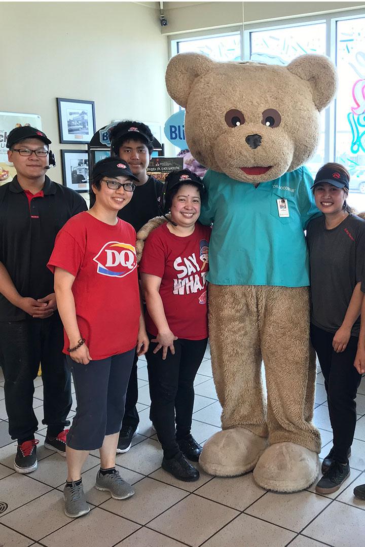 Membres de l'équipe de Dairy Queen avec une mascotte ours