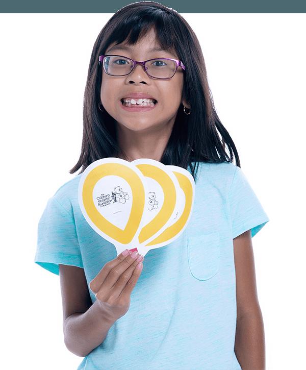 Gianna qui sourit en tenant des ballons du CMN