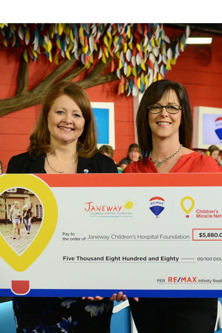 Deux femmes tenant un chèque géant de Remax / CMN pour les Fondations Janeway