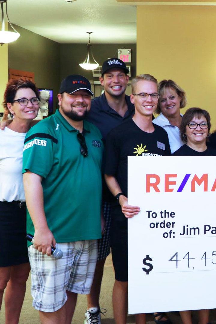 Groupe tenant un chèque géant de Remax pour Jim Pattison