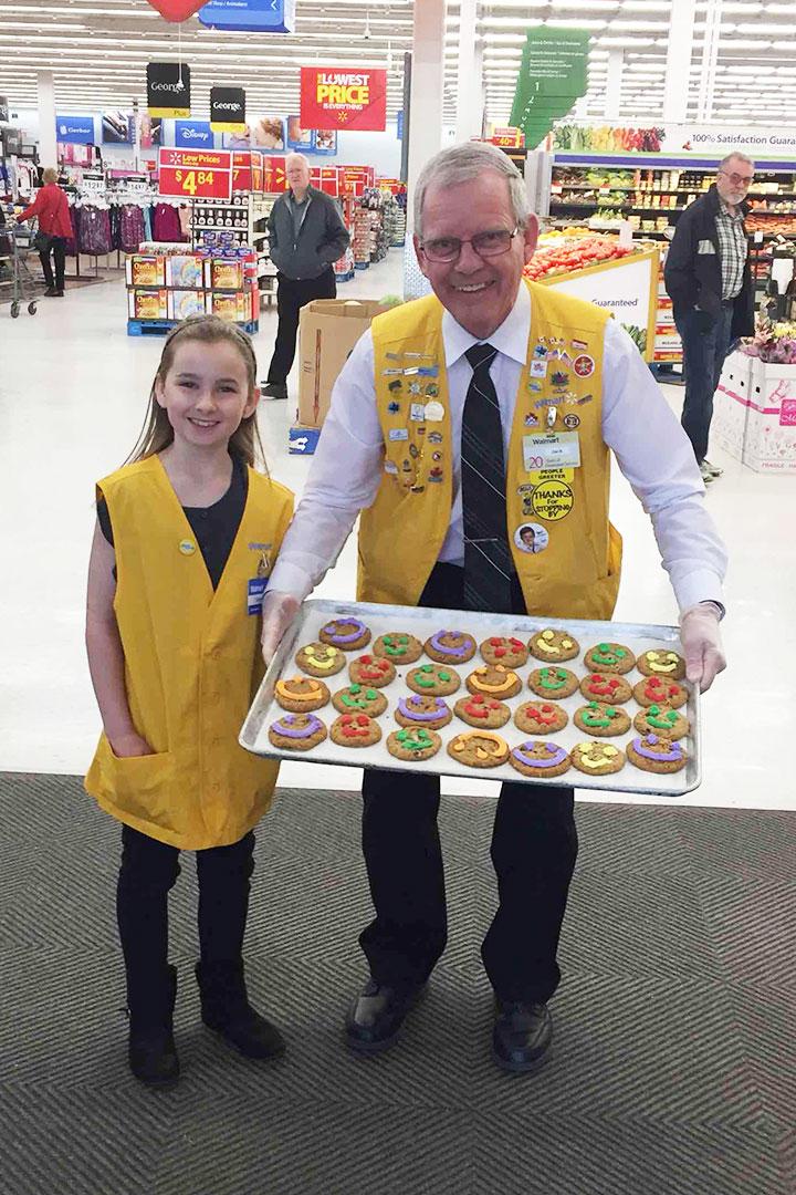 Homme et jeune fille tenant un plateau de biscuits à bonhomme sourire