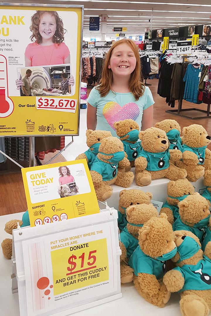 Jeune fille souriant au kiosque de dons d'ours en peluche chez Walmart