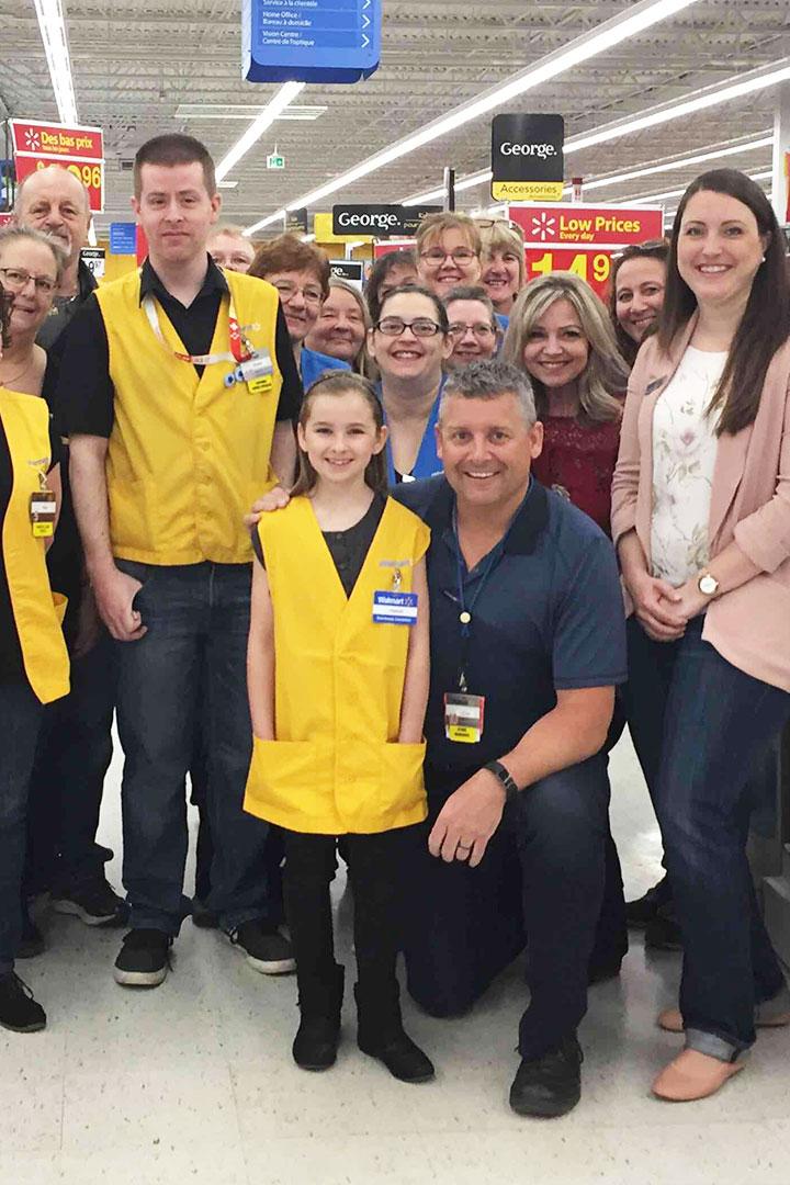 Groupe d'employés de Walmart avec un champion