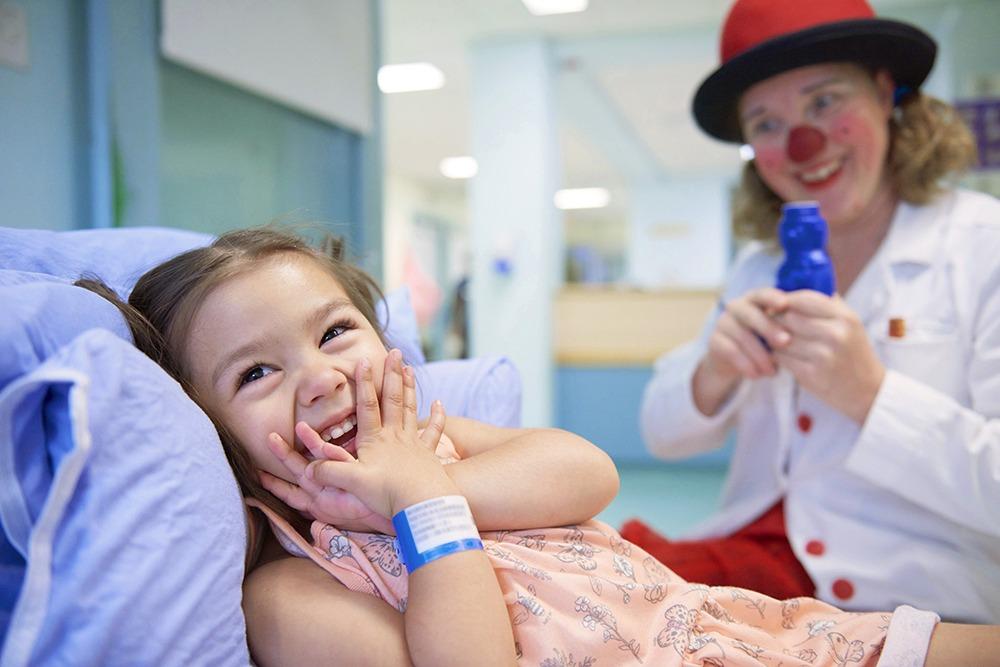 Jeune fille dans son lit d'hôpital riant avec un clown