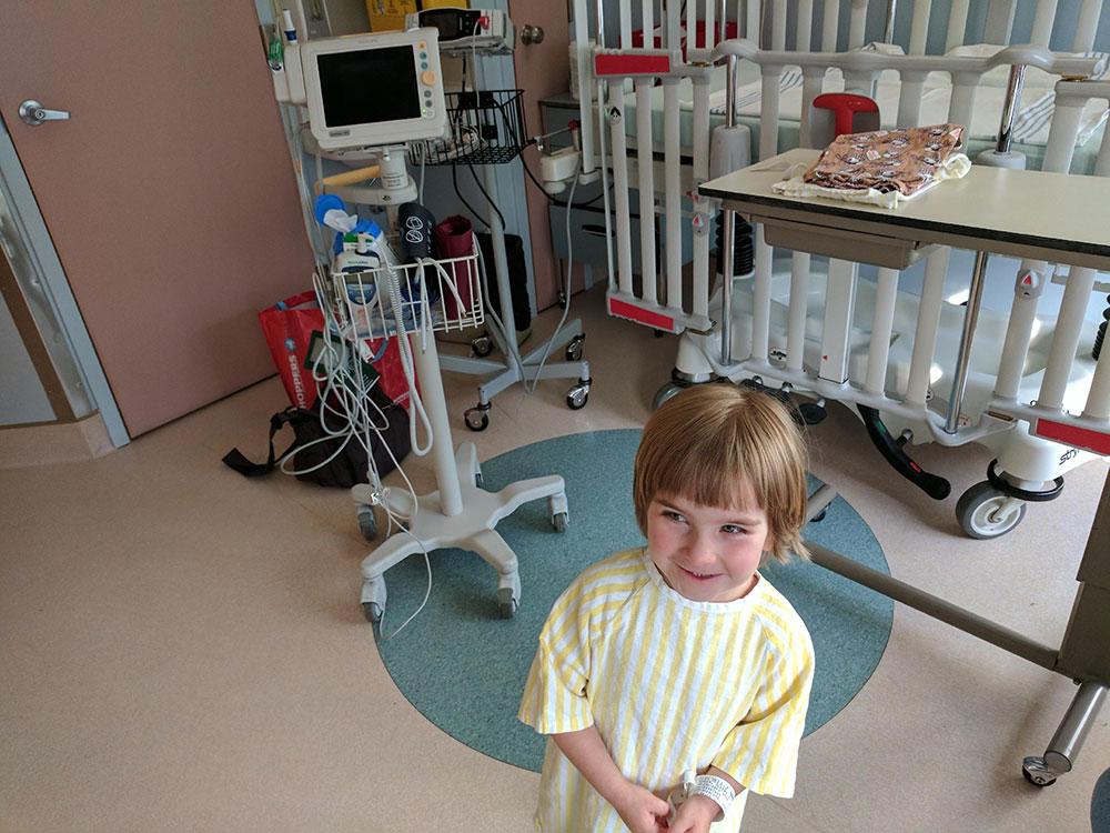 Enfant habillé d'une chemise d'hôpital à rayures jaunes dans une chambre d'hôpital